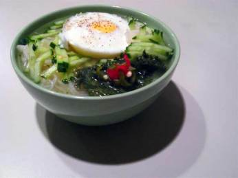 Korean summer noodles with pickled radishes, cucumbers, and poached egg